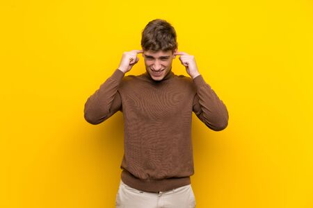 Handsome young man over isolated yellow background frustrated and covering ears
