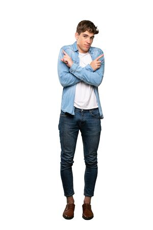 A full-length shot of a Handsome young man pointing to the laterals having doubts over isolated white background