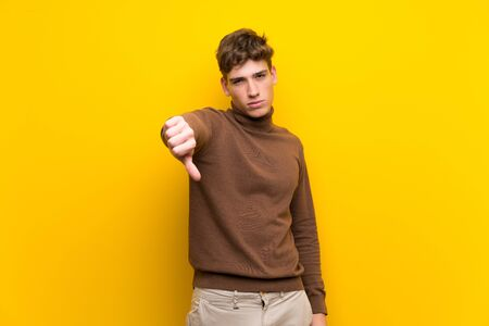 Handsome young man over isolated yellow background showing thumb down with negative expression