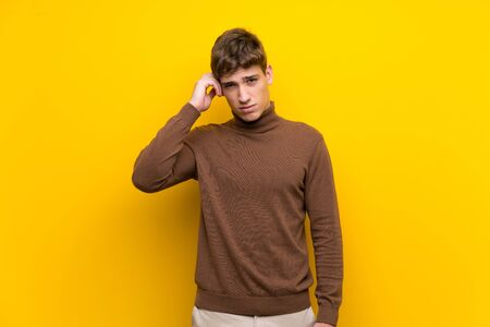 Handsome young man over isolated yellow background having doubts Foto de archivo