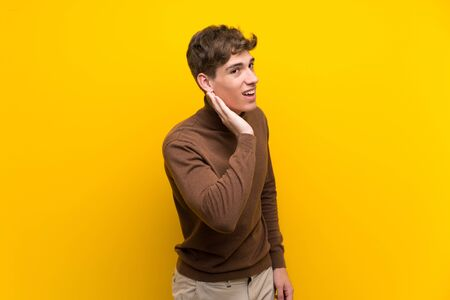 Handsome young man over isolated yellow background listening to something by putting hand on the ear
