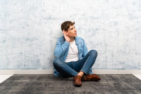 Handsome young man sitting on the floor listening something