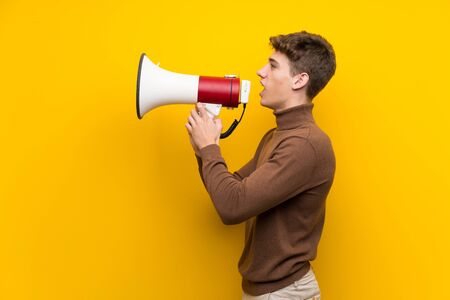 Handsome young man over isolated yellow background shouting through a megaphone