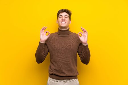 Handsome young man over isolated yellow background in zen pose