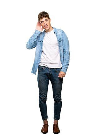 Una foto a figura intera di un bel giovane che ascolta qualcosa mettendo la mano sull'orecchio su sfondo bianco isolato