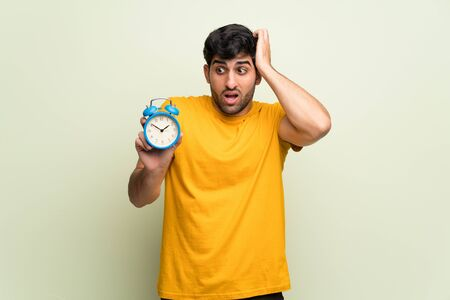Young man over pink wall restless because it has become late and holding vintage alarm clock Stockfoto - 130083128