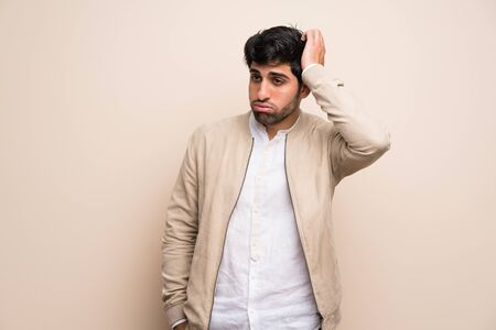 Young man over isolated wall with an expression of frustration and not understanding
