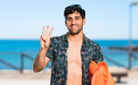Man in trunks happy and counting three with fingers at the beach