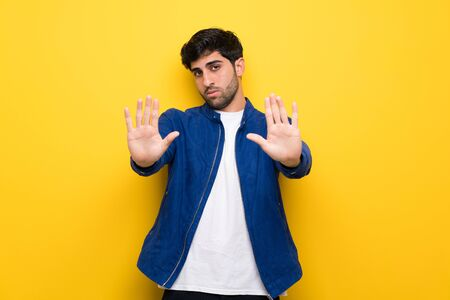 Man with blue jacket over yellow wall making stop gesture and disappointed Stock Photo