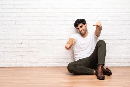 Young man sitting on the floor points finger at you while smiling