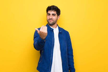 Man with blue jacket over yellow wall inviting to come with hand. Happy that you came