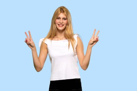 Young blonde woman smiling and showing victory sign with both hands on isolated blue background Reklamní fotografie