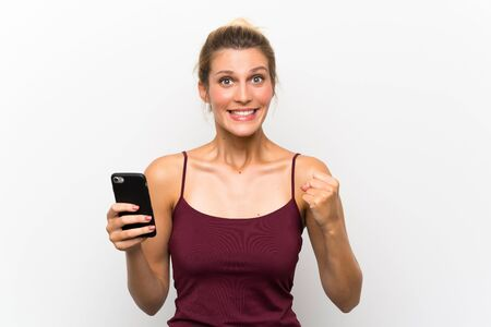 Young blonde woman using mobile phone celebrating a victory