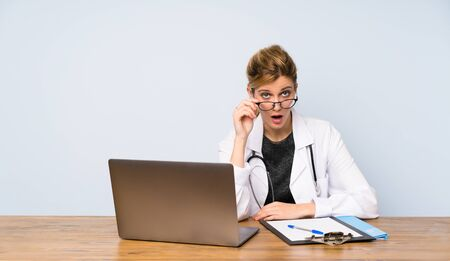 Blonde doctor woman with glasses and surprised