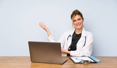Blonde doctor woman extending hands to the side for inviting to come Фото со стока