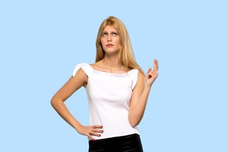 Young blonde woman with fingers crossing and wishing the best on isolated blue background