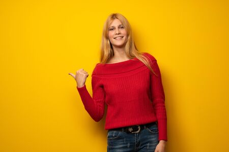 Blonde woman over yellow wall pointing to the side to present a product