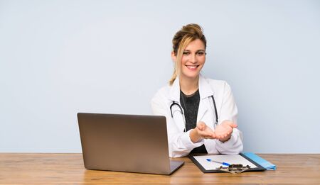 Blonde doctor woman holding copyspace imaginary on the palm to insert an ad Фото со стока