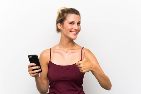 Young blonde woman using mobile phone giving a thumbs up gesture Zdjęcie Seryjne