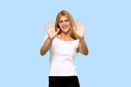 Young blonde woman counting ten with fingers on isolated blue background