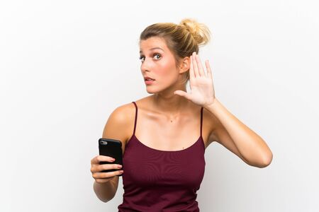 Young blonde woman using mobile phone listening something