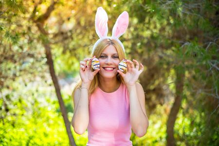young blonde woman wearing bunny ears and with colorful Easter eggs and making a joke