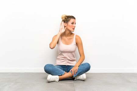 Young blonde woman sitting on the floor listening something