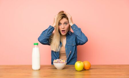 Young blonde woman with bowl of cereals with surprise facial expression Stock fotó - 130162623