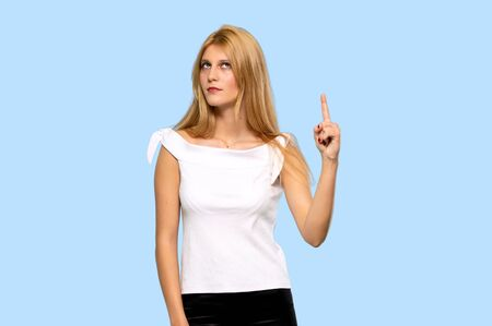 Young blonde woman showing and lifting a finger in sign of the best on isolated blue background