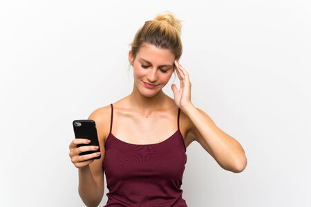 Young blonde woman using mobile phone unhappy and frustrated with something. Negative facial expression