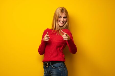 Blonde woman over yellow wall pointing to the front and smiling Stock Photo