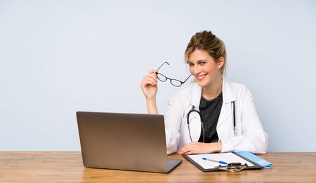Blonde doctor woman with glasses and happy