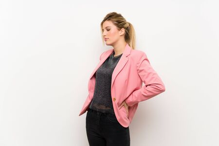 Young blonde woman with pink suit suffering from backache for having made an effort