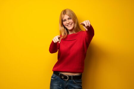 Blonde woman over yellow wall points finger at you while smiling