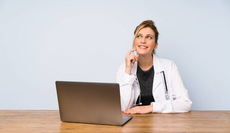 Blonde doctor woman thinking an idea while looking up