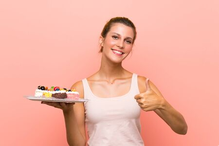 Young blonde woman holding lots of different mini cakes with thumbs up because something good has happened