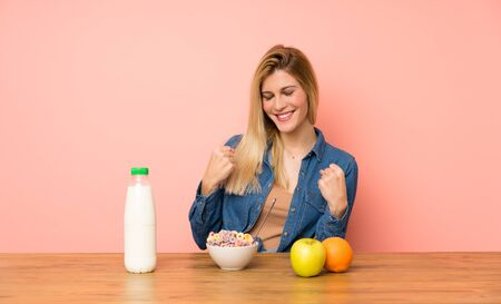 Young blonde woman with bowl of cereals celebrating a victory