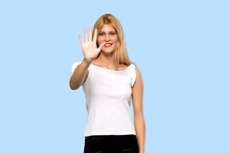 Young blonde woman happy and counting three with fingers on isolated blue background Zdjęcie Seryjne