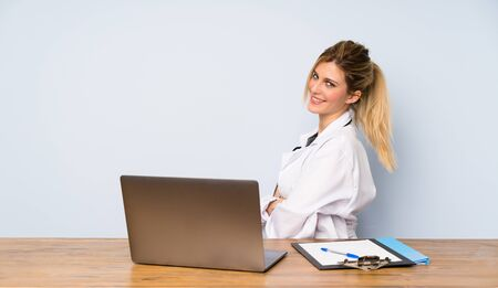 Blonde doctor woman with arms crossed and looking forward Фото со стока