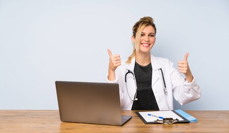 Blonde doctor woman with thumbs up gesture and smiling Фото со стока