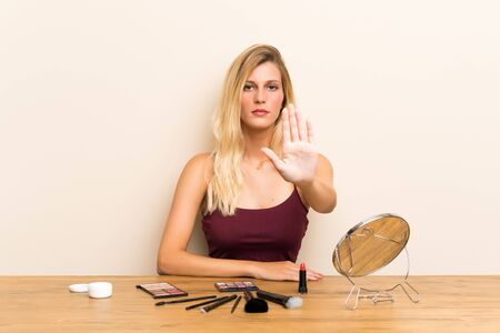 Young blonde woman with cosmetic in a table making stop gesture with her hand
