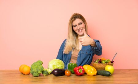 Young blonde woman with many vegetables with thumbs up because something good has happened Zdjęcie Seryjne