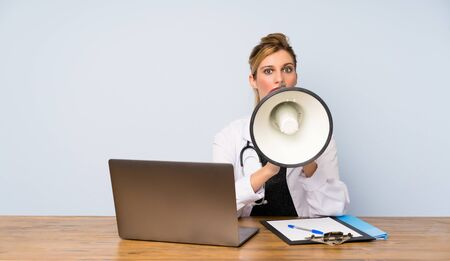 Blonde doctor woman shouting through a megaphone