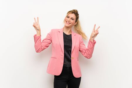 Young blonde woman with pink suit showing victory sign with both hands