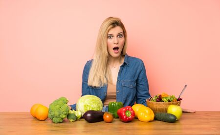 Young blonde woman with many vegetables with surprise facial expression