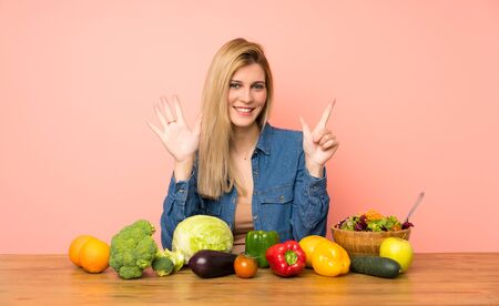 Young blonde woman with many vegetables counting seven with fingers