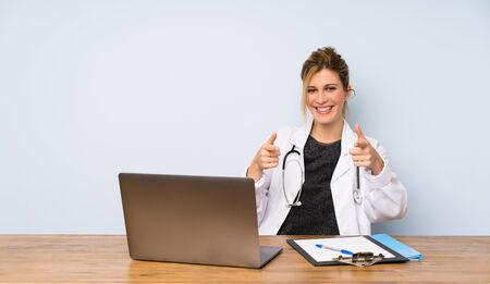 Blonde doctor woman pointing to the front and smiling