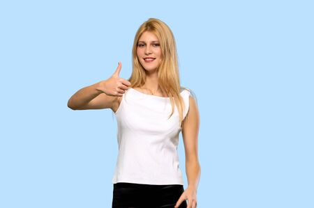 Young blonde woman giving a thumbs up gesture with both hands and smiling on isolated blue background