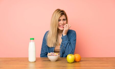 Young blonde woman with bowl of cereals nervous and scared