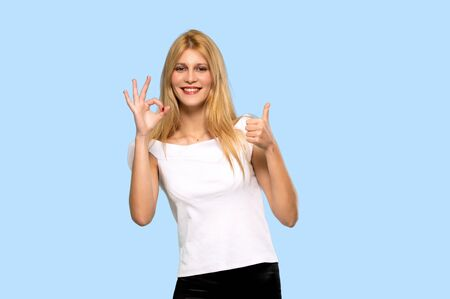 Young blonde woman showing ok sign with and giving a thumb up gesture on isolated blue background